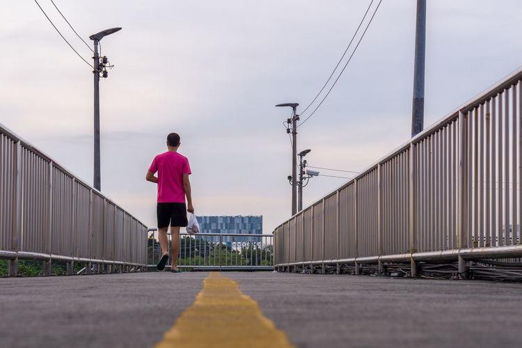 Rear view of man walking on bridge against sky
