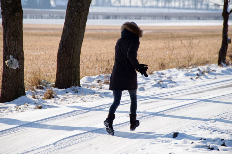 Full length of woman running on snow covered field