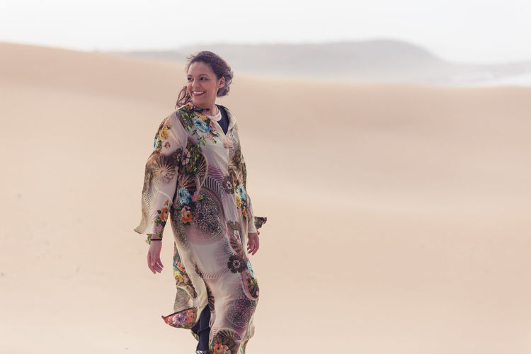 Walk on Horizon Desert Adult Beach Clothing Desert Desert Beauty Floral Pattern Front View Hairstyle Land Leisure Activity Lifestyles Model Nature One Person Outdoors Real People Sand Sky Smiling Standing Three Quarter Length Traditional Clothing Women Young Adult