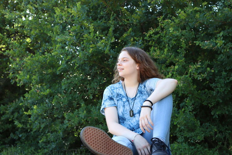 Young woman looking away while sitting on tree
