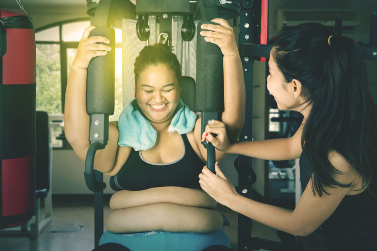 Happy young woman exercising with trainer at gym