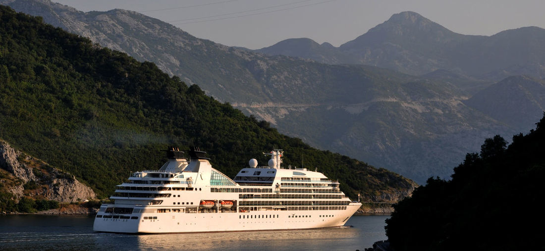 Scenic view of cruise ship against mountains