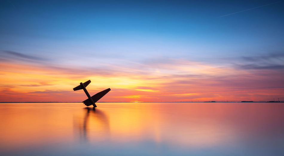 War monument, Harderwijk Netherlands Seascape Landscape Plane Monument Netherlands Harderwijk Freedom Horizon Horizon Over Water Orange Color Cloud - Sky Reflection Sea Beauty In Nature Tranquility Tranquil Scene Water Silhouette Sky Sunset Full Frame Reinaroundtheglobe