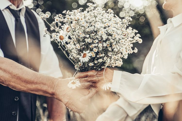 Midsection of people holding flower bouquet