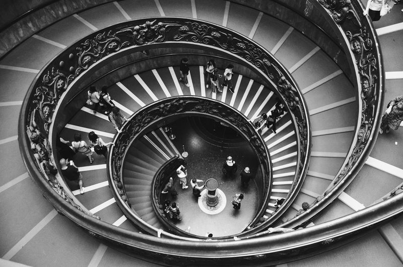 High Angle View Of People On Spiral Staircase In Building
