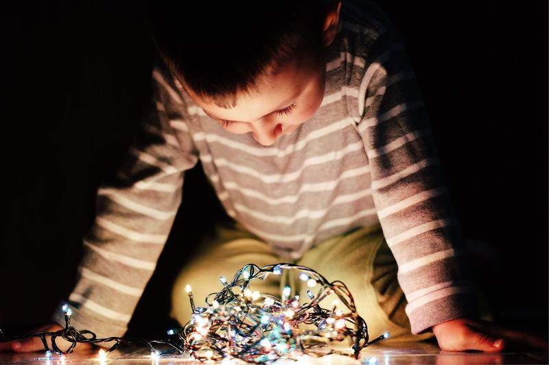 Boy Looking Illuminated String Lights At Home