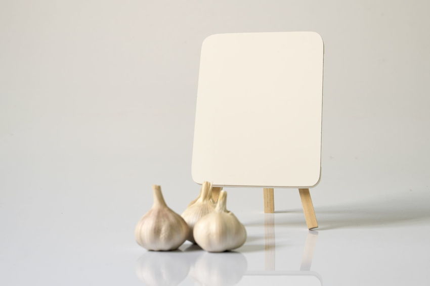 Garlic and blank white board over a white background Blank Cooking Copy Space Day Freshness Garlic Herb Indoors  Ingredient No People Spice White Background White Board White Color