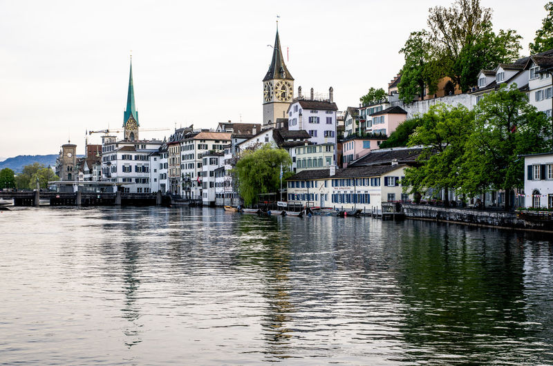 Churches and buildings by limmat river in city against clear sky