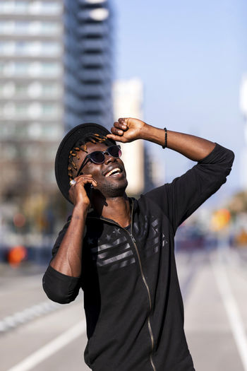 Front view of black man with sunglasses and hat standing against cityscape on the street while using a mobile phone in sunny day. One Person Young Adult Waist Up City Standing Front View Focus On Foreground Men Young Men Casual Clothing Architecture Lifestyles Day Adult Building Exterior Beard Real People Holding Outdoors Arms Raised Human Arm Standing Sunglasses Hat Smiling Laughing City Mobile Phone Cellphone Phone Conversation Communication Street Daylight Bright Sunny Expression Citylife Talking Speaking Calling