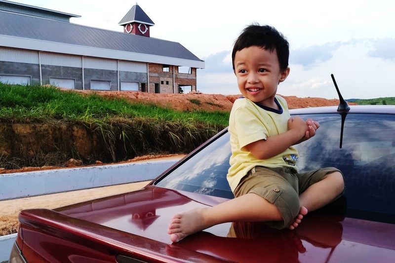 A boy lay on the car bonet Happy Boy Red Car Nice Moment EyeEm Selects Portrait Child Childhood Males  Boys Smiling Looking At Camera