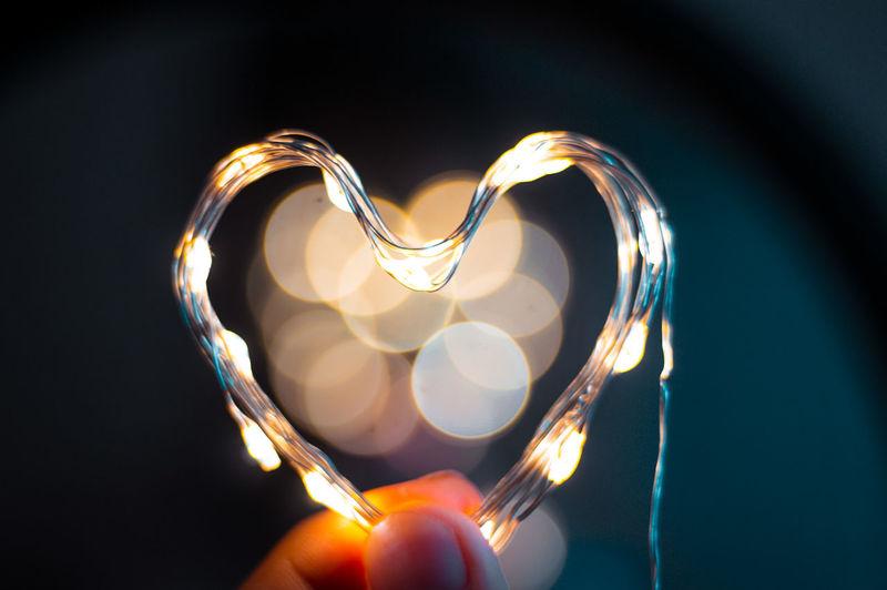 Close-up of hand holding heart shape illuminated lighting equipment