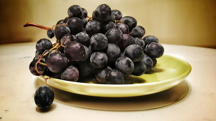 Close-up of black grapes in plate on table