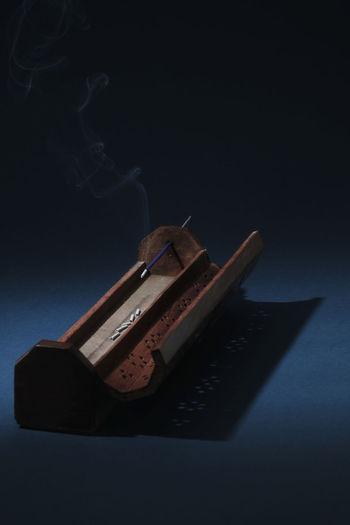 Close up of incense holder against black background