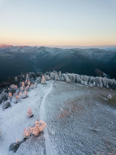 Scenic view of snow covered land against clear sky during sunset