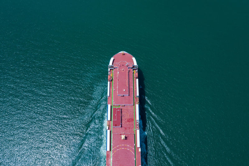 Aerial view ro-ro ship loading new cars. automotive container carriers sailing on the sea