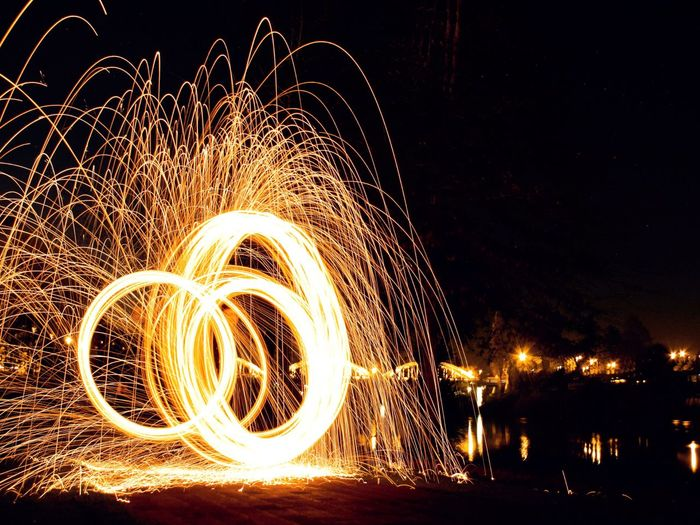 Illuminated Wire Wool In Motion At Riverbank Against Clear Sky At Night