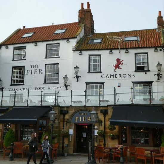 The Pier Inn, Whitby, North Yorkshire. Built in victorian times overlooking the busy harbour. Architecture Restaurant British Pub Built Structure Social Venue Pub Sign Traditional Architecture Traditional Culture Whitby Public House Building Exterior Architecture Outdoors Passers By Text Day Outdoor Seating Social Venue