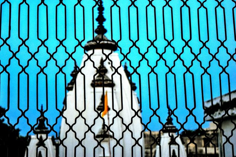Historic temple against clear blue sky seen through silhouette fence