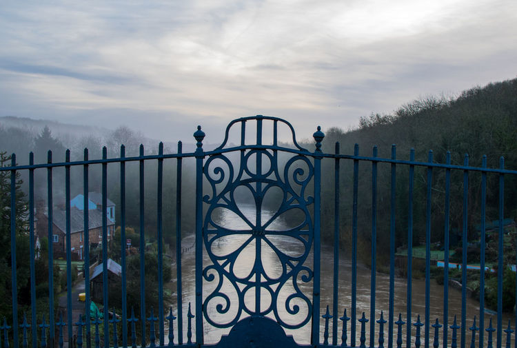 Closed gate in front of river amidst trees against cloudy sky