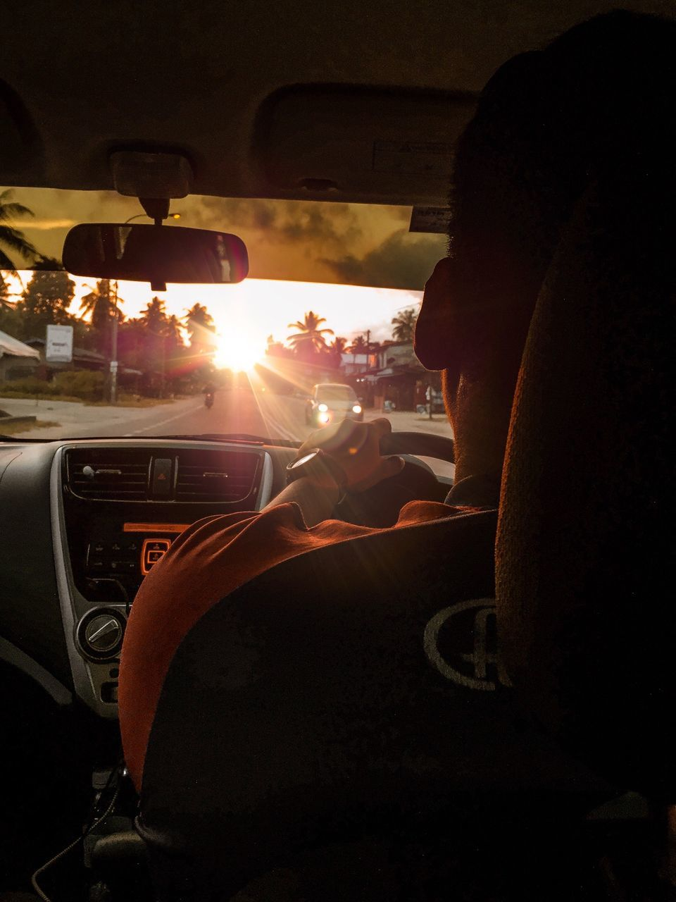 car, mode of transportation, transportation, vehicle interior, motor vehicle, one person, real people, car interior, land vehicle, driving, windshield, men, lifestyles, travel, glass - material, indoors, steering wheel, control panel, rear view, lens flare, road trip