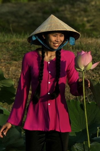 Woman holding purple while standing against plants
