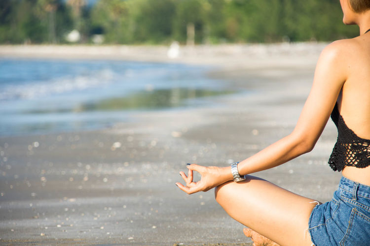 Young Woman Doing Yoga At Beach