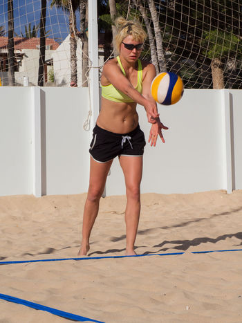 Attractive sporty women is serving the beach volleyball Fitness, Activity Attaktive, Ball Beach Beach Volleyball Beachball Beautiful Bump Dig Female, Hit Jump Matches Outdoor Outdoors Play Recreation, Served Sport Sports Sportswear, Sporty Volleyball Woman