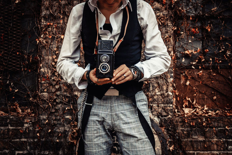 Unrecognizable photographer using vintage medium format photo camera while photographing outdoors.