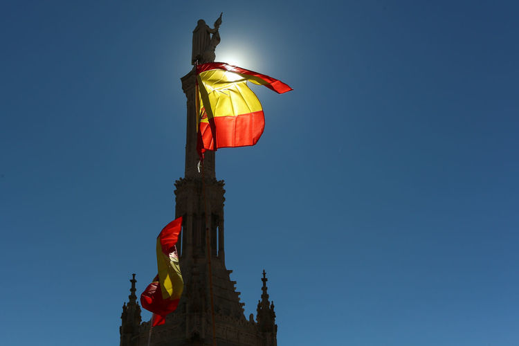 Low angle view of flag statue against clear blue sky