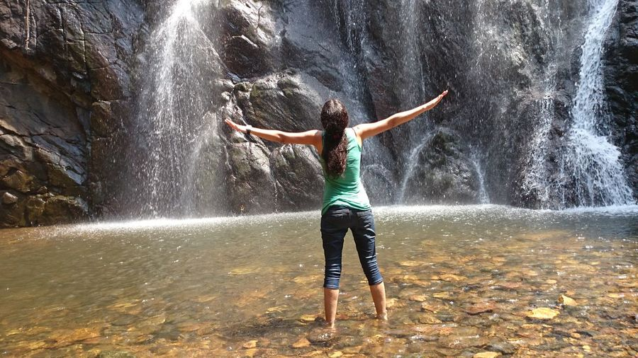 Full length rear view of woman with arms outstretched standing against waterfall