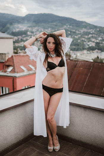 Portrait of woman wearing lingerie while standing on terrace