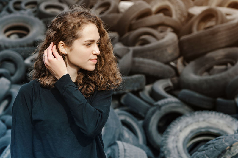 Young woman standing by tires