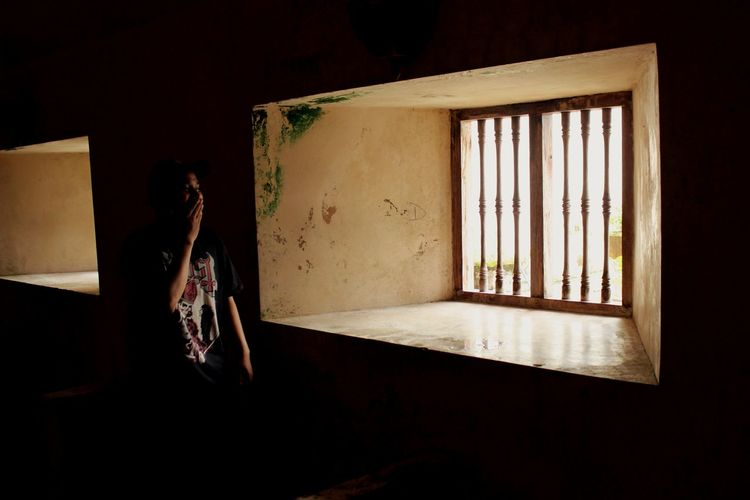 Woman standing by window at old house