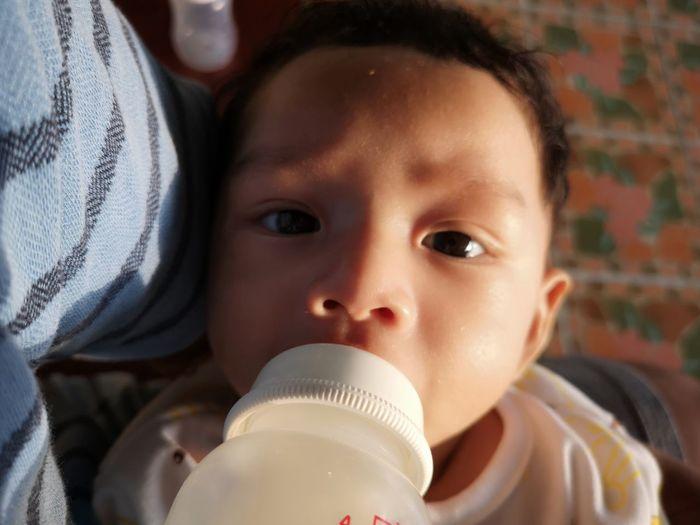 Close-up portrait of cute boy drinking bottle