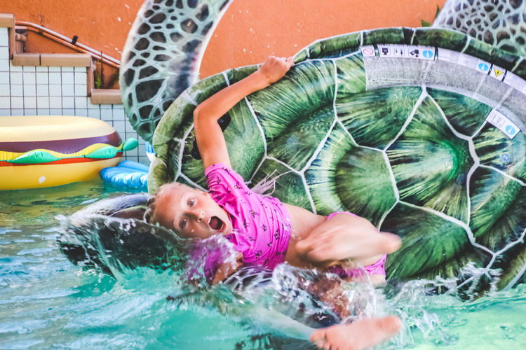 young girl having fun in the pool, falling off an inflatable Water One Person Nature Leisure Activity Child Women Day Real People Enjoyment Pool Portrait Swimming Childhood Lifestyles Swimming Pool Smiling Outdoors Inflatable  Floating On Water Splash Falling Vacations Girls Summertime
