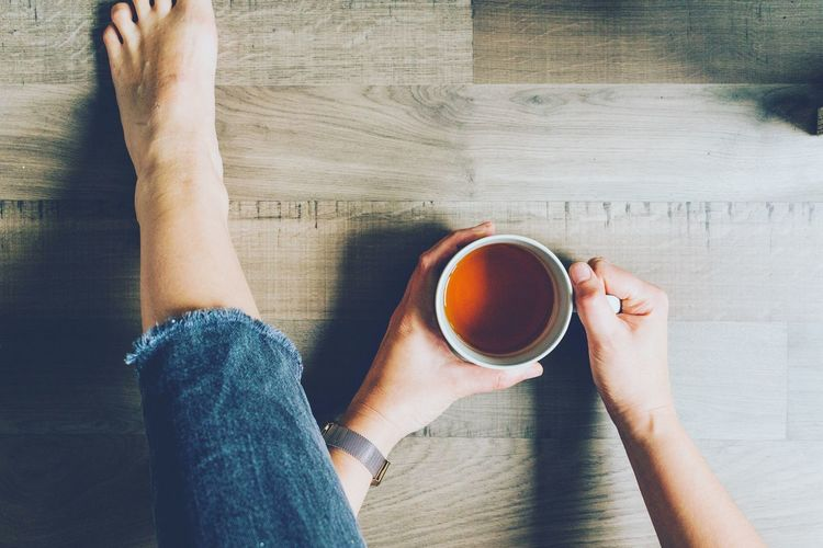 Low section of woman holding coffee cup on floor