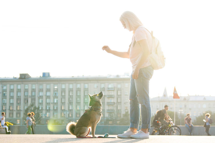 Full length of woman standing by dog in city against clear sky