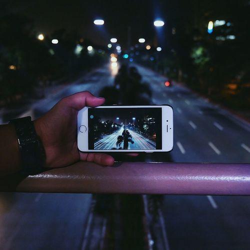 Person holding illuminated lighting equipment at night