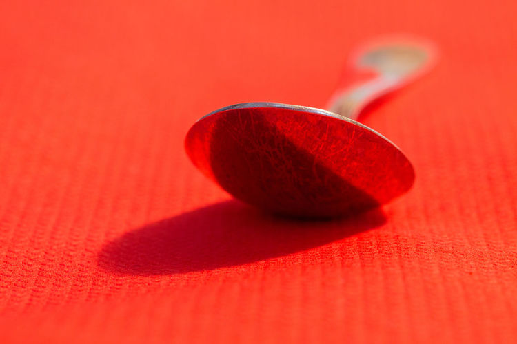 Close-up of spoon on orange table