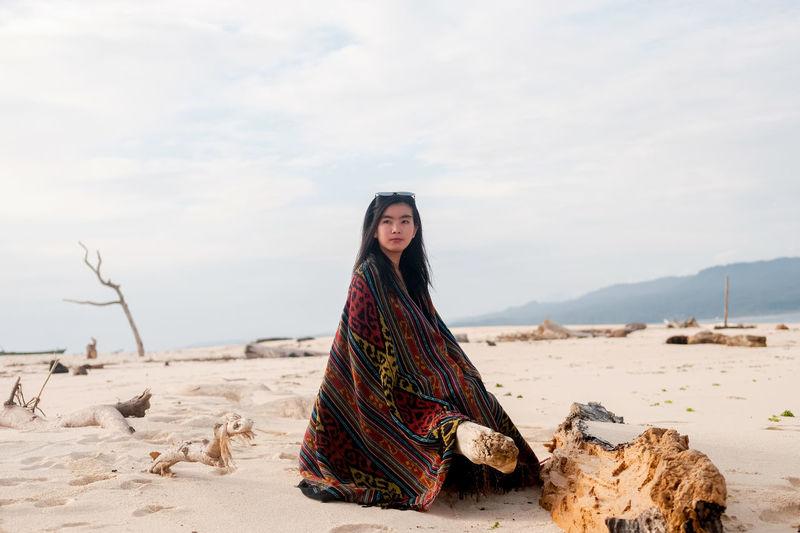 Portrait of woman sitting on beach of banana island  against sky