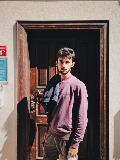 Portrait of young man standing at door