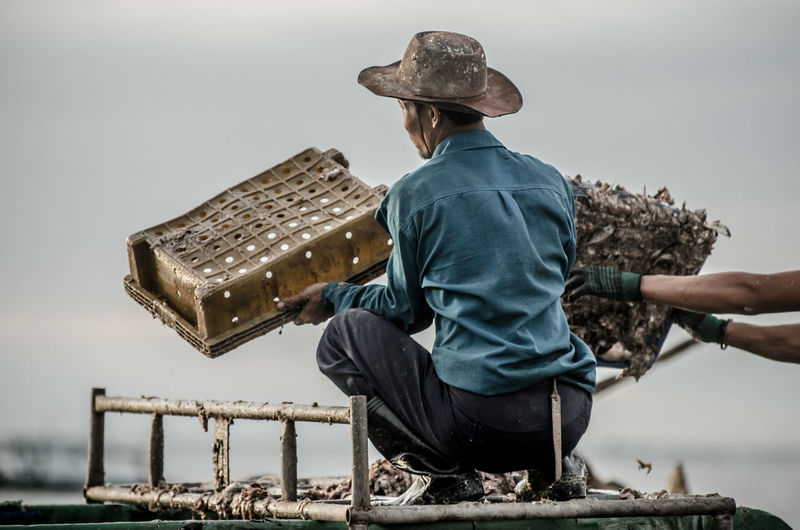 Worker holding fish basket