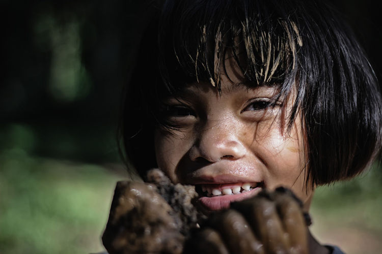 Close-up portrait of girl covered in mud