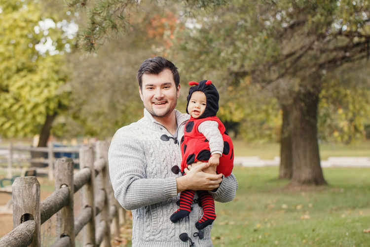 Portrait of smiling father carrying cute daughter while standing in park