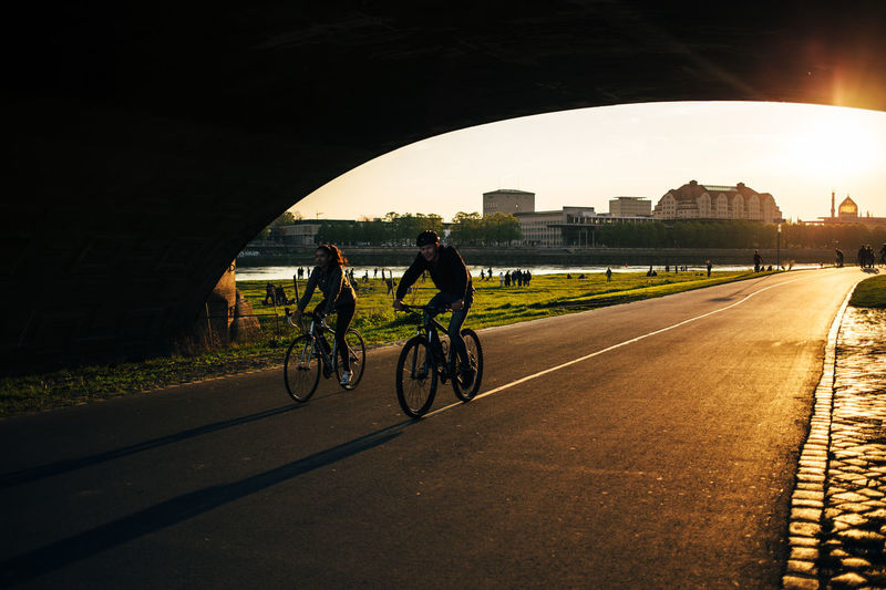 Men riding bicycle on road in city against sky