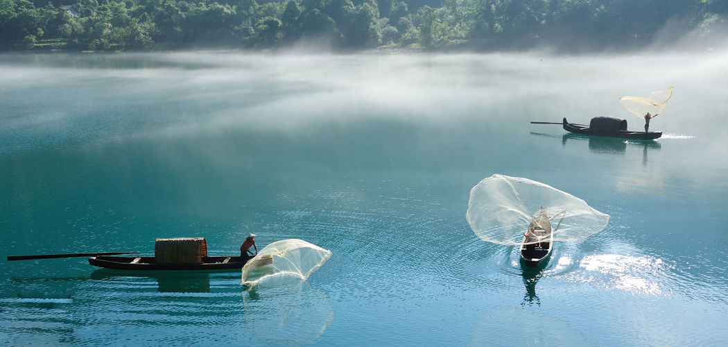 Fishermen throwing net in river