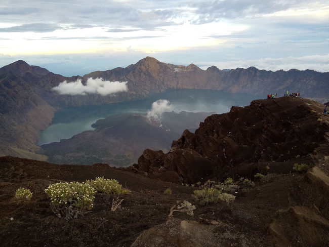Rinjani volcano's crater lake shortly after dawn Active Volcano Beauty In Nature Cloud - Sky Day Dramatic Landscape Environment Geology Idyllic Landscape Mountain Mountain Range Nature No People Outdoors Power In Nature Remote Rock Scenics - Nature Sky Tranquil Scene Tranquility Travel Travel Destinations Volcanic Crater Water