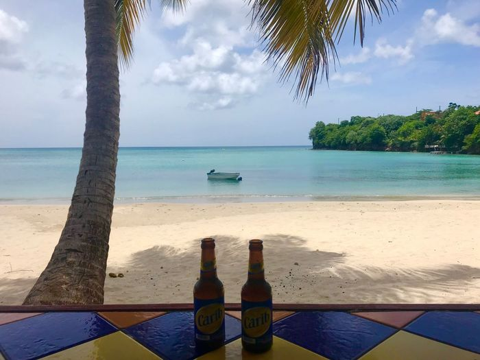 Heaven is a beach bar on Grenada 💕 Caribbean Beach Caribbean Sea Grenada Beer Bottles On The Beach Beer Bottles Palm Tree, Beach, Sea And Boat Palm Tree On Beach Palm Tree White Sand Beach Coloured Tiles Caribbean Island Sea Water Sky Land Cloud - Sky Beach Tree