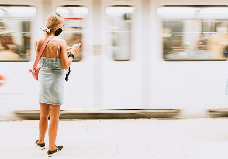 Rear view of woman walking on train at railroad station
