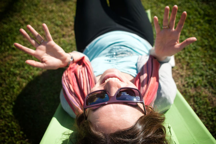 High angle view of happy woman lying on slide at playground